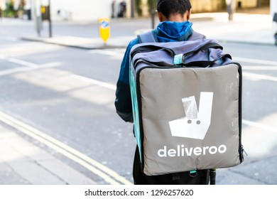 London, UK - September 13, 2018: Deliveroo backpack man with blue sign in Knightsbridge area of city during day delivering food closeup by street road