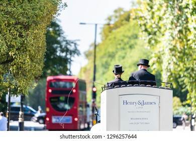 London, UK - September 13, 2018: Street with horse tour traditional carriage and cars in traffic on road by Kensington during sunny day with sign for Belgravia office
