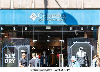 London, UK - September 13, 2018: Street road in Chelsea shopping with people standing walking by blue Columbia Sportswear Company entrance exterior of sports store