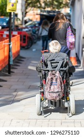 London, UK - September 13, 2018: People on street by road pavement sidewalk in Chelsea or Belgravia with vertical view of one disabled senior man or woman riding on wheelchair