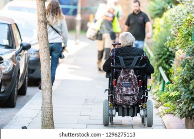 London, UK - September 13, 2018: People on street by road pavement sidewalk in Chelsea or Belgravia with one disabled senior man or woman riding on wheelchair
