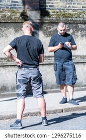 London, UK - September 13, 2018: Street in Belgravia area with candid men two security guards standing looking at phones on pavement vertical view