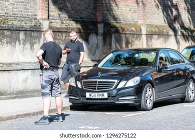 London, UK - September 13, 2018: Street in Belgravia area with candid men two security guards standing with phone on pavement by parked car