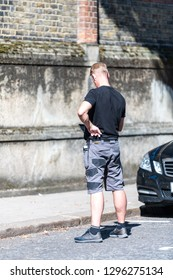 London, UK - September 13, 2018: Street in Belgravia area with candid man security guard standing with phone on pavement by car