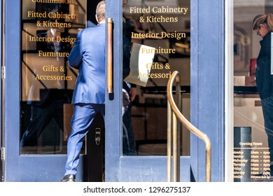 London, UK - September 13, 2018: Street in Belgravia area with business man entering Linley furniture store with blue architecture