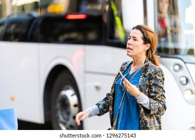 London, UK - September 13, 2018: Street in Belgravia area with candid woman walking on pavement with traffic white bus in blurry defocused background on busy day