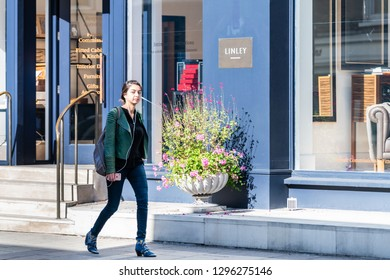London, UK - September 13, 2018: Street in Belgravia area with young woman walking on sidewalk pavement by Linley store with blue architecture