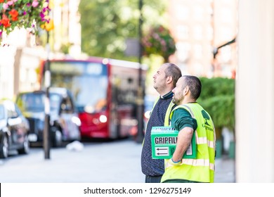 London, UK - September 13, 2018: Street in Belgravia area with two men construction workers standing looking up with defocused background