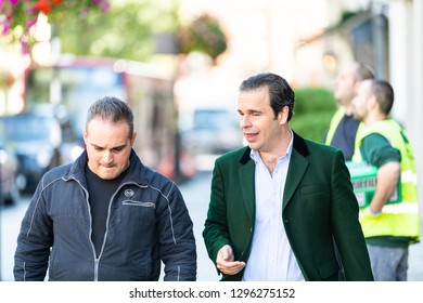 London, UK - September 13, 2018: Street in Pimlico Chelsea or Belgravia area with two men pedestrians business friends walking on pavement talking closeup