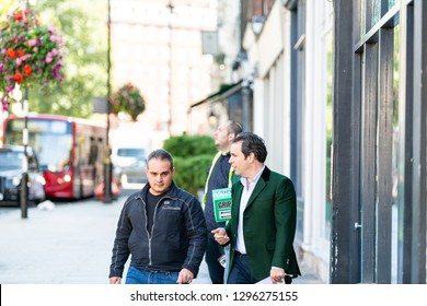 London, UK - September 13, 2018: Street in Pimlico Chelsea or Belgravia area with two men pedestrians business friends walking on pavement talking during day