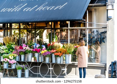 London, UK - September 13, 2018: Street in Pimlico Belgravia area with Wild at Heart Florist flower shop and woman setting up bouquets