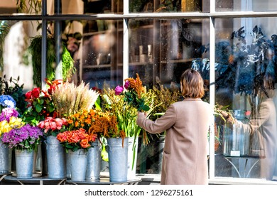 London, UK - September 13, 2018: Street in Pimlico Belgravia area with Wild at Heart Florist flower shop and closeup of woman setting up bouquets