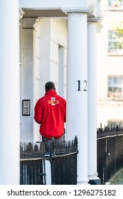 London, UK - September 13, 2018: Pimlico area with buildings and man Royal Mail delivery man standing by house flat