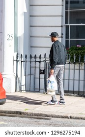 London, UK - September 13, 2018: Pimlico area with buildings and man walking carrying grocery bags walking on pavement from Greggs cafe store