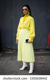 LONDON, UK- SEPTEMBER 13 2019: People on the street during the London Fashion Week. Woman with long hair in sunglasses in a yellow pleated skirt and silk blouse