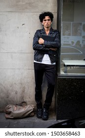 LONDON, UK- SEPTEMBER 13 2019: People on the street during the London Fashion Week. A young man in a black leather jacket, white T-shirt and skin-tight jeans.