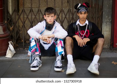 LONDON, UK- SEPTEMBER 13 2019: People on the street during the London Fashion Week. Two teenagers dressed in sports style. One wears black shorts and a sweater like Mickey Mouse.
