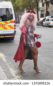 LONDON, UK- SEPTEMBER 14 2018: People on the street during the London Fashion Week. A girl in a short checkered dress, a red leather raincoat, a beret, in net pantyhose, on heels, crosses the road