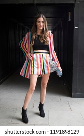 LONDON, UK- SEPTEMBER 14 2018: People on the street during the London Fashion Week. A girl in striped shorts and a jacket, a black top, in black boots posing against the backdrop of an arch.