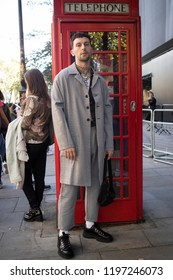 LONDON, UK- SEPTEMBER 14 2018: People on the street during the London Fashion Week. A man in a gray plaid coat and trousers, near a red phone booth