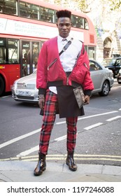 LONDON, UK- SEPTEMBER 14 2018: People on the street during the London Fashion Week. A man in a red bomber jacket, white shirt and checkered scottish trousers.