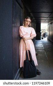 LONDON, UK- SEPTEMBER 14 2018: People on the street during the London Fashion Week. The blonde girl in a pink dress in the sixties style stands by the black wall