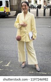 LONDON, UK- SEPTEMBER 14 2018: People on the street during the London Fashion Week. Brunette girl in yellow lemon corduroy pantsuit laughs