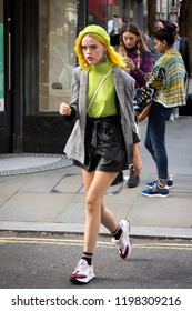 LONDON, UK- SEPTEMBER 14 2018: People on the street during the London Fashion Week. Girl in a yellow beret, with long hair, a blouse, short shorts and a checkered gray blazer walks down the street