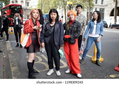 LONDON, UK- SEPTEMBER 14 2018: People on the street during the London Fashion Week. Three girls in red pose together