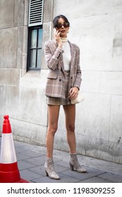 LONDON, UK- SEPTEMBER 14 2018: People on the street during the London Fashion Week. Girl in a classic checkered suit: jacket and short skirt, talking on the phone