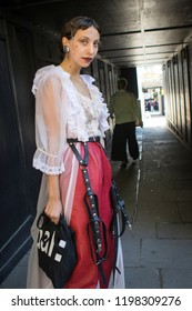 LONDON, UK- SEPTEMBER 14 2018: People on the street during the London Fashion Week. Brunette girl with hairstyle in the style of the twenties, wears a transparent lace blouse and cape, burgundy pants
