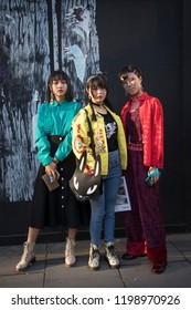 LONDON, UK- SEPTEMBER 14 2018: People on the street during the London Fashion Week. Asian girls posing against the wall in a red, blue and yellow bomber jacket