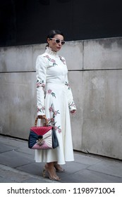 LONDON, UK- SEPTEMBER 14 2018: People on the street during the London Fashion Week. Woman in white long dress with pink flowers and beaded collar posing