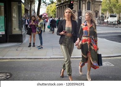 LONDON, UK- SEPTEMBER 14 2018: People on the street during the London Fashion Week. Two girls walk down the street