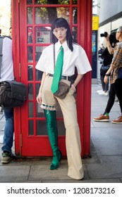 LONDON, UK- SEPTEMBER 14 2018: People on street during London Fashion Week. Famous Chinese blogger poses with her friend. She wears white men's  shirt, green tie, green jackboots plaid pants