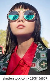 LONDON, UK- SEPTEMBER 14 2018: People on the street during the London Fashion Week. The girl in the red dress shirt, gray jacket and green boots and sunglasses