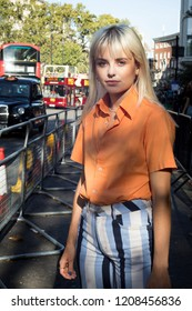 LONDON, UK- SEPTEMBER 14 2018: People on the street during the London Fashion Week. Blonde girl with long hair in light blue jeans and orange t-shirt
