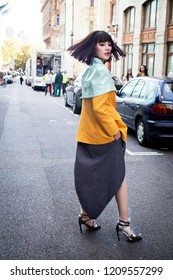 LONDON, UK- SEPTEMBER 14 2018: People on the street during the London Fashion Week. Chinese blogger in a yellow jacket and green cape