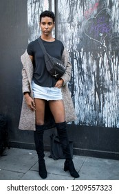 LONDON, UK- SEPTEMBER 14 2018: People on the street during the London Fashion Week. Short cropped curly girl in a short skirt, black top and black boots