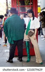 LONDON, UK- SEPTEMBER 14 2018: People on street during London Fashion Week. Famous Chinese blogger poses with her friend. She wears white men's  shirt, green tie, green jackboots and plaid pants.