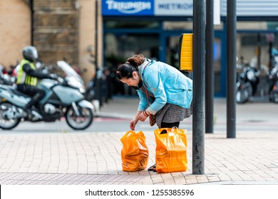 London, UK - September 14, 2018: Neighborhood district of Pimlico with woman and orange Sainsbury's grocery supermarket bags on street sidewalk road during day