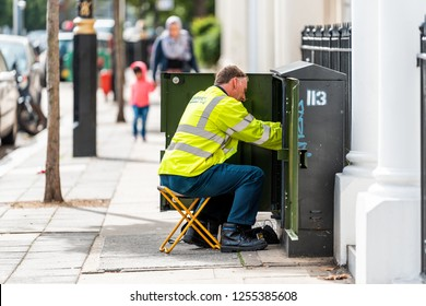 London, UK - September 14, 2018: Neighborhood district of Pimlico with man electrician worker fixing box on street sidewalk road during day