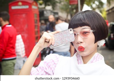 LONDON, UK- SEPTEMBER 14 2018: People on the street during the London Fashion Week. Chinese Fashion blogger Harper Silin in a white blouse and skirt holding red bag in polka