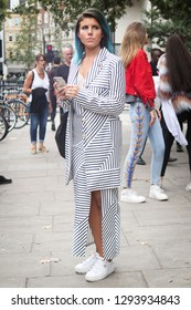 LONDON, UK- SEPTEMBER 14 2018: People on the street during the London Fashion Week. Stunning brunette in a maxi dress with thigh high slit showing off her gorgeous legs