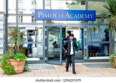 London, UK - September 14, 2018: Street sidewalk pavement in district neighborhood area with entrance sign for Pimlico Academy and people walking