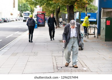 London, UK - September 14, 2018: Street sidewalk pavement in Pimlico district neighborhood area with old man walking with cane crutches disabled senior