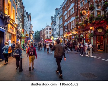 LONDON, UK - SEPTEMBER 15, 2018: View of the historic architecture of London in the United Kingdom at night by Leicester  Square with lots of tourists and locals passing by.