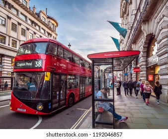 LONDON, UK - SEPTEMBER 15, 2018: View of London in the UK at sunset showcasing its historic architecture by Piccadilly Circus with the famous double decker red bus.