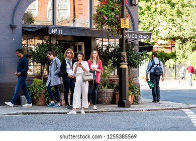 London, UK - September 15, 2018: Neighborhood district of Pimlico, people waiting to cross street road at crosswalk by store during sunny day
