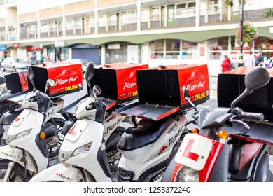 London, UK - September 16, 2018: Row of many Pizza Hut online delivery scooters, motorcycles parking, parked by road street curb in Pimlico with nobody